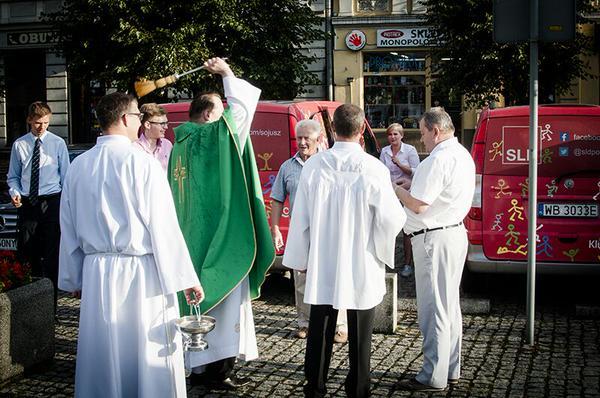 Kampanijne wozy SLD poświęcone przez księdza
