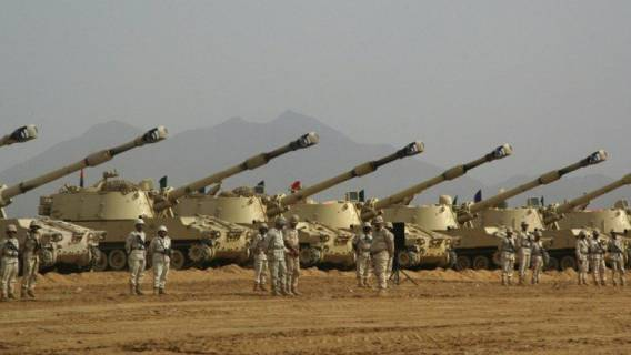 Saudi soldiers stand at attention in fro
